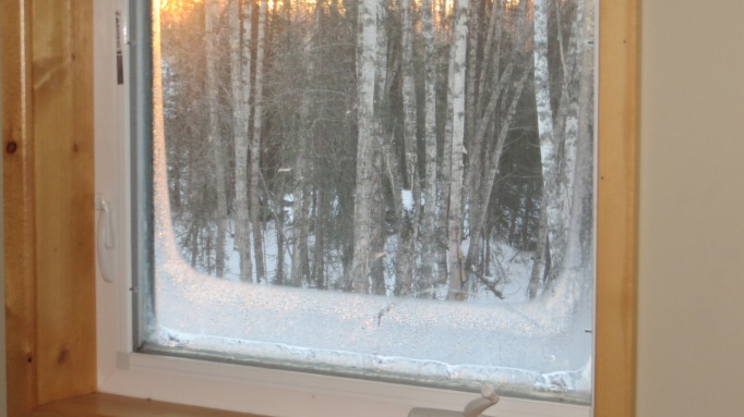 Just rising sun illuminates a south facing window and highlights the amount of condensation followed by ice at the edges; outside air temp -7.7 F