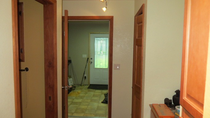 Looking east down the hallway into the mud room and the front door